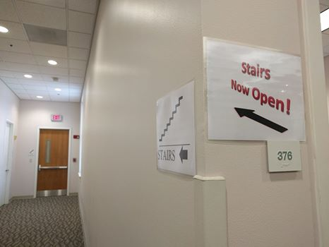 "Hallway leading to stairwell marked by sign saying ""Stairs Now Open!"""