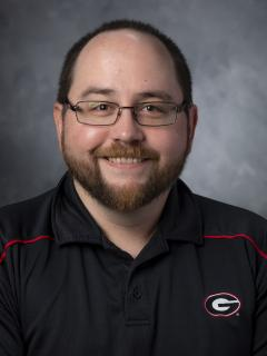 "Bearded man with glasses wearing a black golf shirt with the the UGA ""Big G"" logo on it."