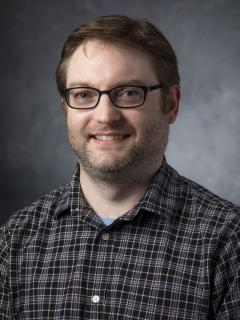Man with short light brown hair wearing glasses and a plaid button up shirt.