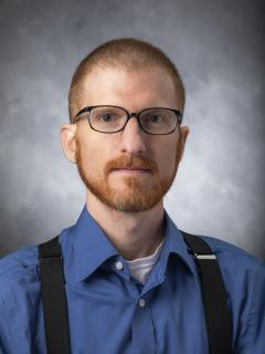 Man with shaved red hair and beard wearing glasses, a blue button up shirt, and overalls.